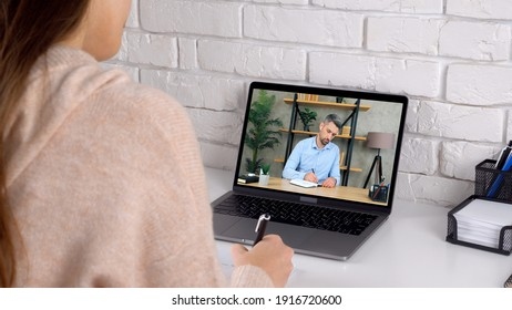 Businesswoman and businessman managers at home office work together communication remote online conference video call chat laptop computer webcam writes information in notebook, quarantine pandemic