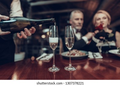 Businesswoman and Businessman . Old Business People .Successful Old People. Relax together. Romantic Meeting, Rich People. Couple Resting in Restaurant. Luxury Life. Waiter pouring champagne