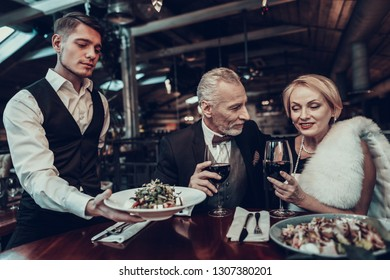 Businesswoman and Businessman. Old Business People .Successful Old People. Relax together. Romantic Meeting, Rich People. Couple Resting in Restaurant. Luxury Life. service staff. Waiter brings dishes