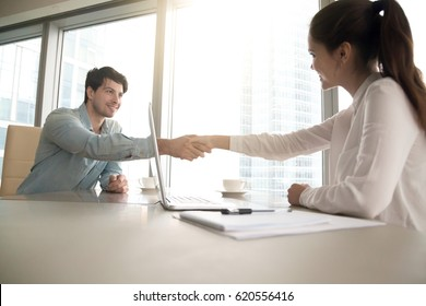Businesswoman and businessman shaking hands over the table with laptop and papers at the office, pleasant business meeting, starting negotiation, conducting job interview