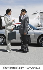 Businesswoman and businessman standing in front of convertible and talking