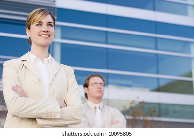 businesswoman and businessman standing side by side with arms folded looking forward