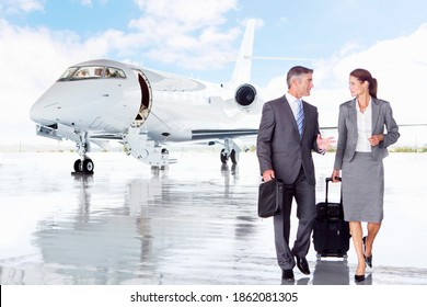 Businesswoman and Businessman talking while walking away from a private jet