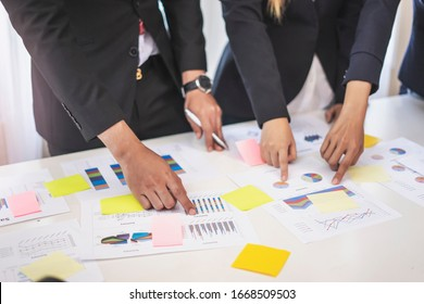 businesswoman and businessman working together in a group in an office, all pointing on the paper together in teamwork conversing and planning strategy using data and statistics of charts and graphs