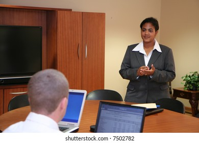 Businesswoman and Businessmen looking at a computer during presentation