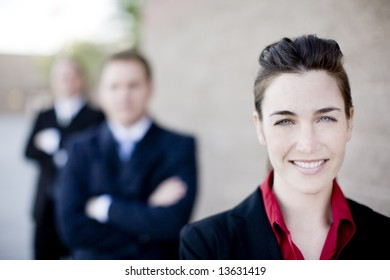 businesswoman and businessmen wearing formal wear standing in line smiling
