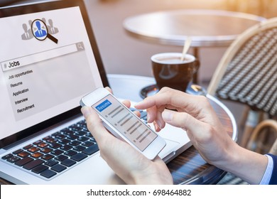 Businesswoman at cafe searching for job and career opportunities online with smartphone and laptop computer and sending resume for application, HR concept, close-up on hands