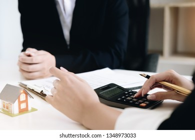 Businesswoman calculating budget before signing real estate project contract with house model at the table in the office