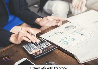 Businesswoman calculating and discussing financial documents - assessment and evaluation concepts