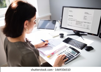 Businesswoman calculating tax at desk in office