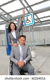 Businesswoman calling out a taxi for man in wheelchair