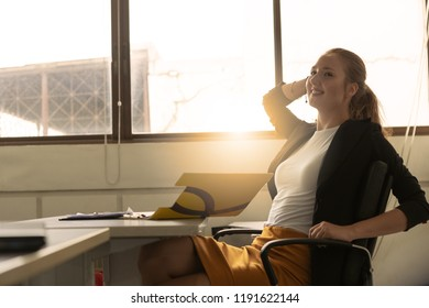 Businesswoman calm and smiling relaxing on her comfortable chair at the office. She satisfied after her work done, enjoying break with eyes closed, peace of mind with no stress.