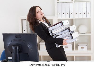 Businesswoman Carrying Stack Of Folders In Office