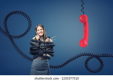 A businesswoman caught and bound by large black telephone cords near a giant red phone receiver. Call-center job. Multitasking at work. Working with clients.