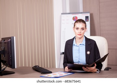 Businesswoman with a chart folder in hands in her office