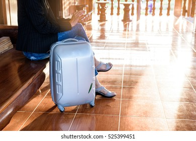 Businesswoman chatting mobile phone while waiting for someone with her suitcase