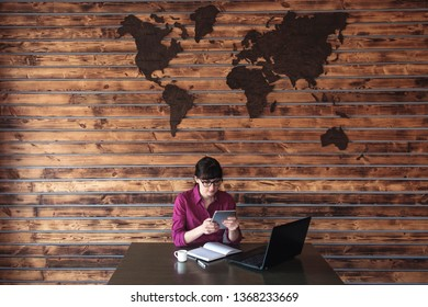 Businesswoman checking her tablet computer as she sits at her laptop in a modern office with world map on the wood timbered wall