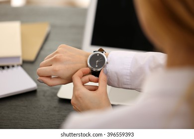 Businesswoman checking the time on her wrist watch, close up