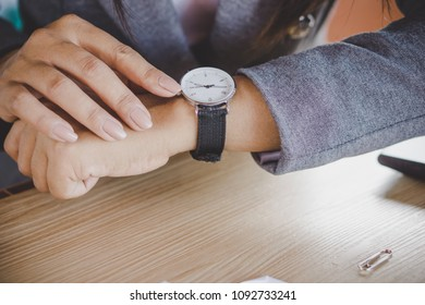 businesswoman checking the time on watch at her office waiting for someone coming late