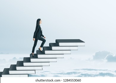 Businesswoman climbing book pile ladder. Sky background. Education and promotion concept