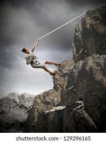 businesswoman climbing steep mountain hanging on rope