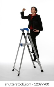 Businesswoman climbing a stepladder with a determined expression on her face shaking her fist at the ceiling