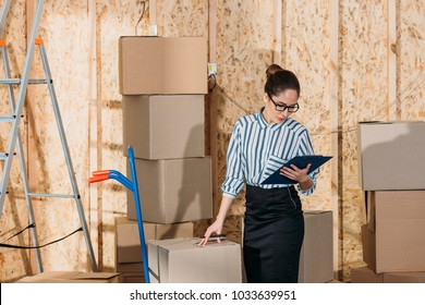 Businesswoman with clipboard checking delivery packages
