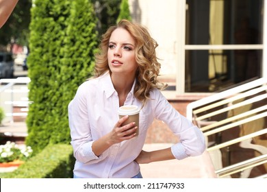 Businesswoman with coffee on city street