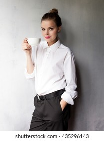 Businesswoman with coffee or tea cup looking away. Businesswoman smiling and holding tea cup on lunch break after meeting