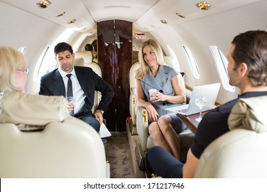 Businesswoman with colleagues having drinks on private jet