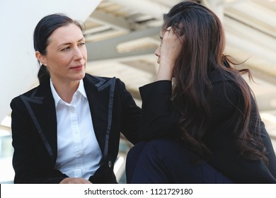 Businesswoman consoling her friend that suffering from headache about problem working, female is frustrated about work and friend's hand on shoulder of colleagueat outside building