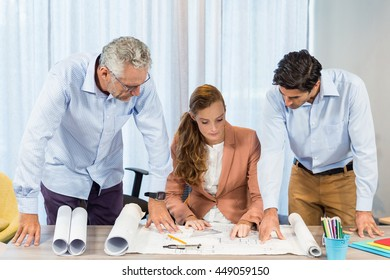 Businesswoman and coworkers discussing blueprint in the office