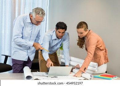 Businesswoman and coworkers discussing blueprint using laptop in the office
