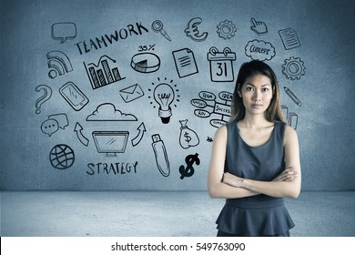 Businesswoman with crossed arms against grey room