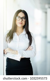 Businesswoman crossed hands portrait in office with panoramic windows.