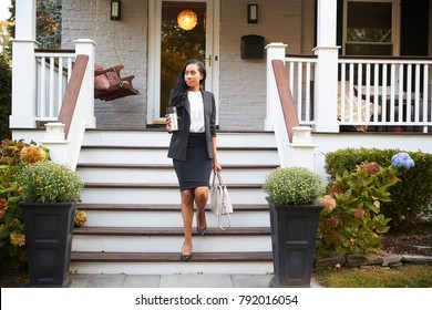 Businesswoman With Cup Of Coffee Leaving Suburban House For Work