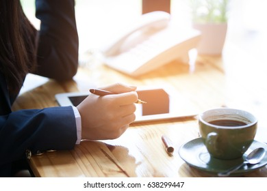 Businesswoman discussing the analysis charts or graphs on modern White office desk table and using smart phone and laptop.Business analysis and strategy concept