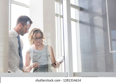 Businesswoman discussing with businessman over document at office