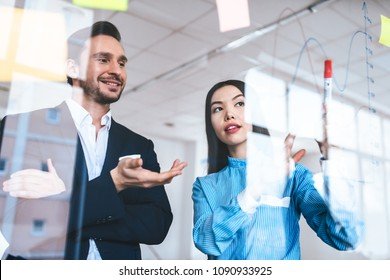The businesswoman discussing with a man near the glass