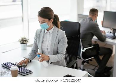 Geschäftsfrau desinfiziert ihre Laptop-Tastatur im Büro.