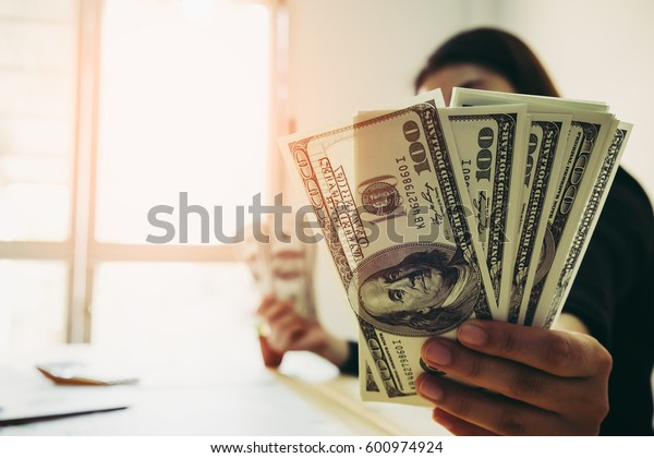 Businesswoman displaying a spread of cash over a green vintage background