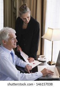 Businesswoman with documents looking a male colleague use laptop at home office desk