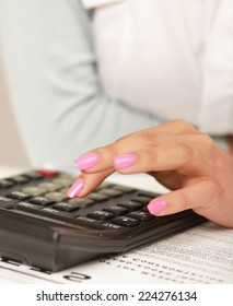 Businesswoman doing some paperwork at her desk using a calculator