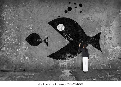 businesswoman drawing  big fish eat small fish on the wall