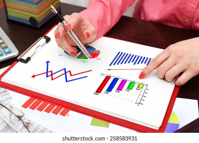 businesswoman drawing business charts on clipboard