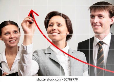 Businesswoman drawing a graph on a glass window in an office