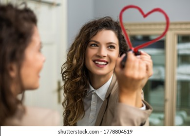 Businesswoman is drawing heart with lipstick on the mirror while preparing for work.