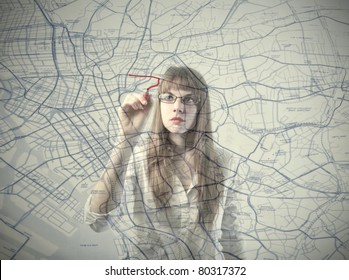 Businesswoman drawing a route on a city map