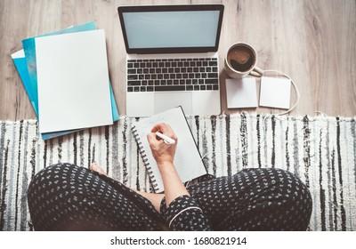 Empresaria vestida de pijama escribiendo plan de día disfrutando del café matutino en la oficina del piso de la sala de estar con laptop, papeles y otras cosas de primera vista. Trabajo a distancia en el concepto de tiempo de cuarentena mundial