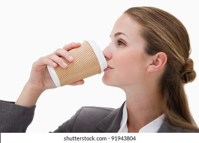 Businesswoman drinking a takeaway coffee against a white background